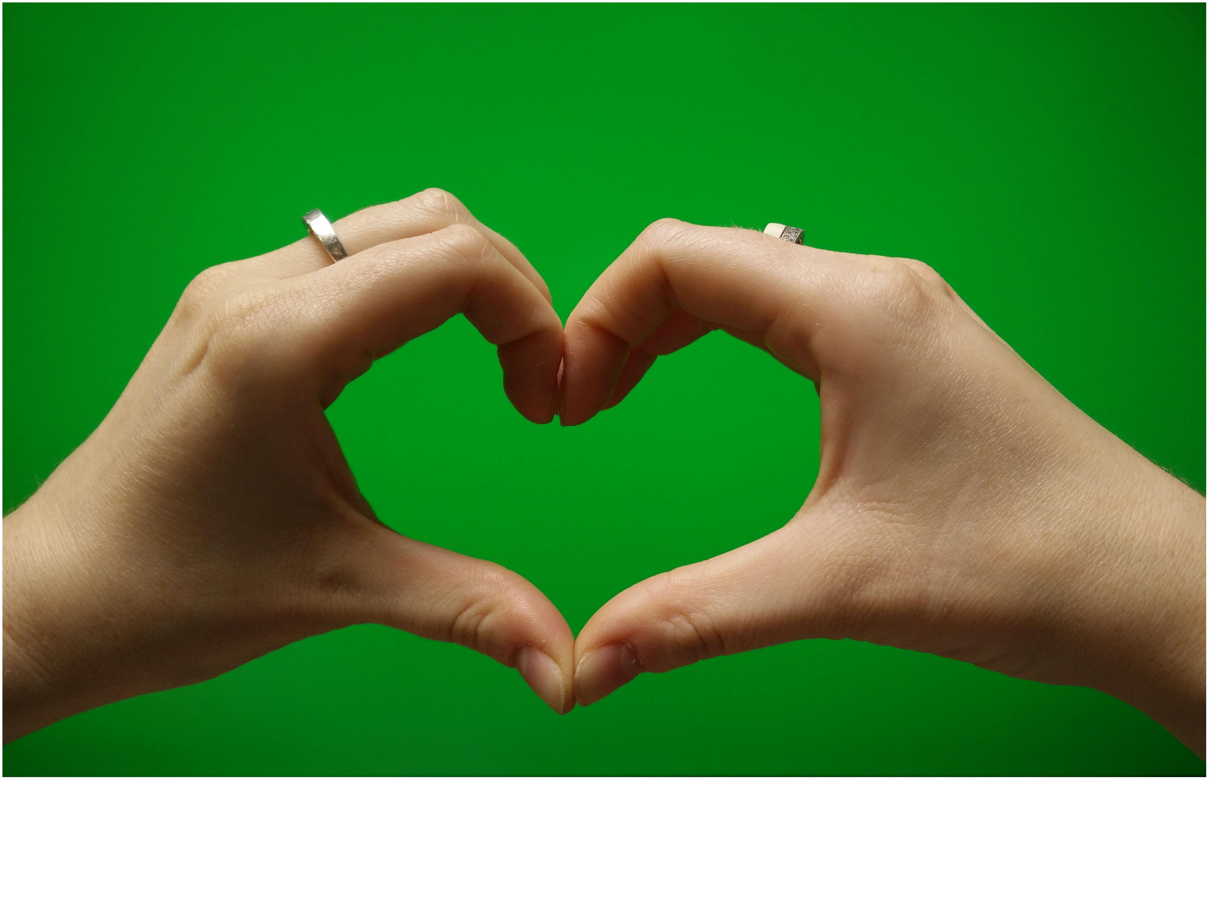 Coeur avec les mains sur fond vert Photos