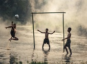 Enfants jouant au football Photos